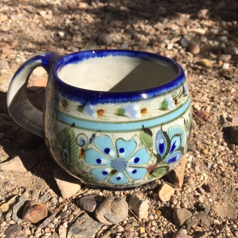 Ken Edwards Collection series coffee mug.  Blue rim with green, two shades of blue and brown flowers, birds, and butterflies decorated on the side or inside on bowls or plates.