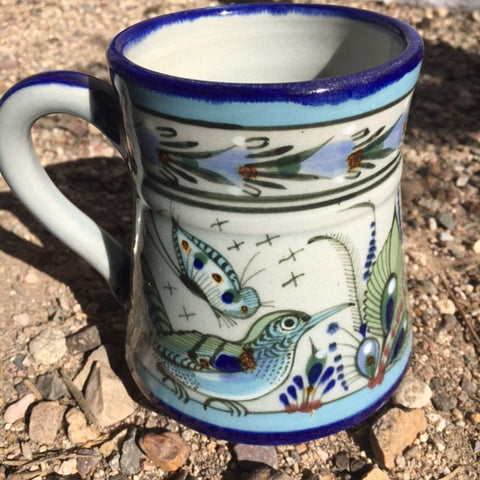 Ken Edwards Collection Coffee or Tea mug with green, two shades of blue and brown flowers, birds, and butterflies decorated on the side or inside on bowls or plates