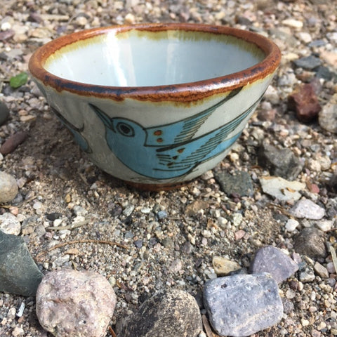 Ken Edwards custard or soup cup.  It is natural grey clay color background with birds, butterflies, and leaves in blue, green, black and brown on the outside.