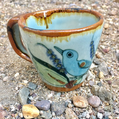 This beautiful mug is natural grey clay color with brown rim and handle and the outside is decorated with blue birds and green leaves.