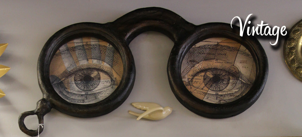 Vintage iron wall art shaped like glasses, with illustrations of eyes inside