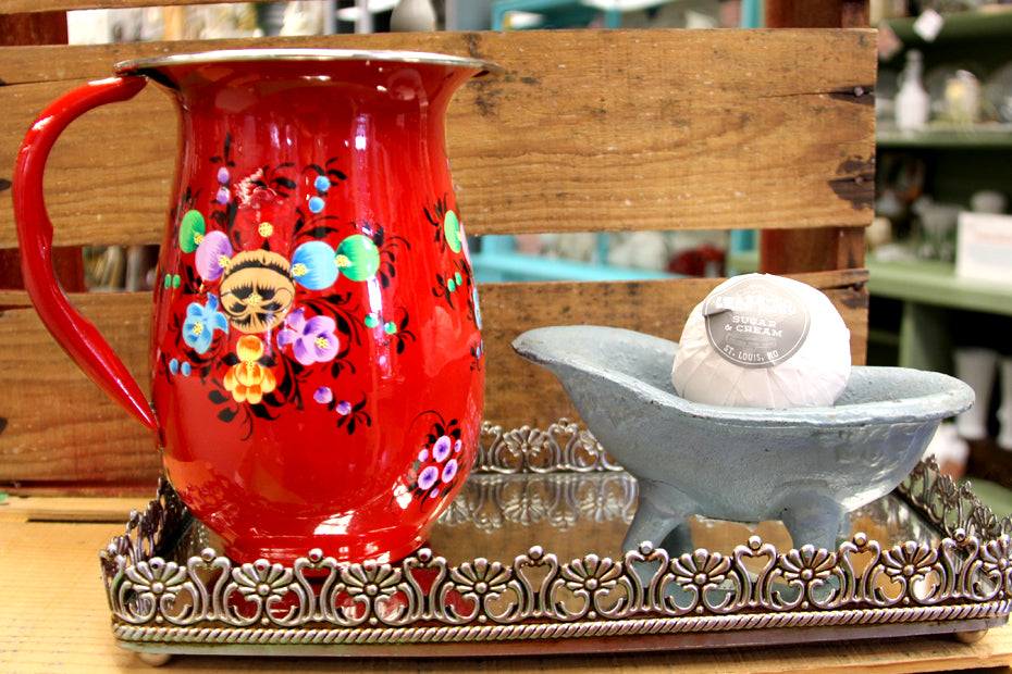 Red floral water pitcher with miniature bath tub holding bath fizz