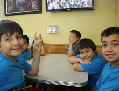 Children from FLOCK flashing the peace sign