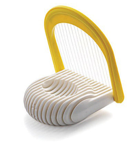 The white egg slicer stands on the table with the yellow handle open and an indentation in the middle to place the egg.
