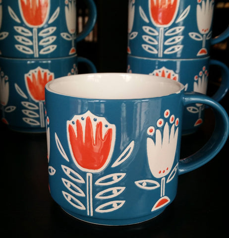 The blue mug with the orange and white tulip design is shown sitting in front of two mugs with the same design.