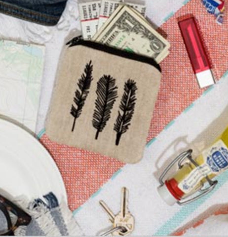 """Feather"" zippee coin pouch with dollar bills and movie tickets sticking out of it laying next to a set of keys, bottle filled with yellow liquid and red and white perfume spritzer on a red and white background."