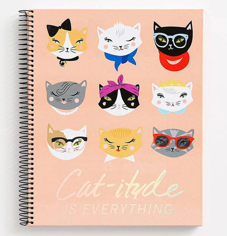 "The Spiral 9x11 ""Catitude"" Notebook features a pink cover with cats heads in a variety of styles and words that reads,""Cat-itude is Everything"" in gold foil."