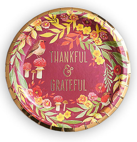 "These are red paper plates that display the words, ""Thankful & Grateful"", and surrounding the words are greenish yellow leaves, red flowers, and red mushrooms with a robin sitting on one of them."