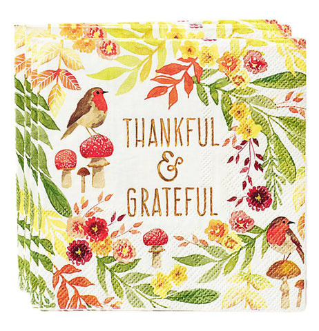 "This set of four cream colored napkins feature the words, ""Thankful & Grateful"" and show designs of red flowers, green leaves, and red mushrooms, one of which has a robin bird sitting on it."