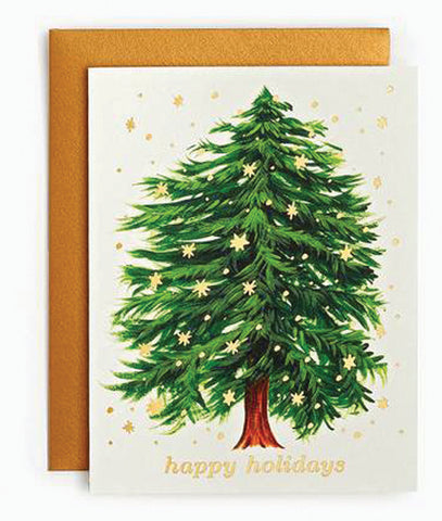 "A card with an evergreen tree with stars falling around it over the text ""Happy Holidays"" on a white background sits on a brown envelope."