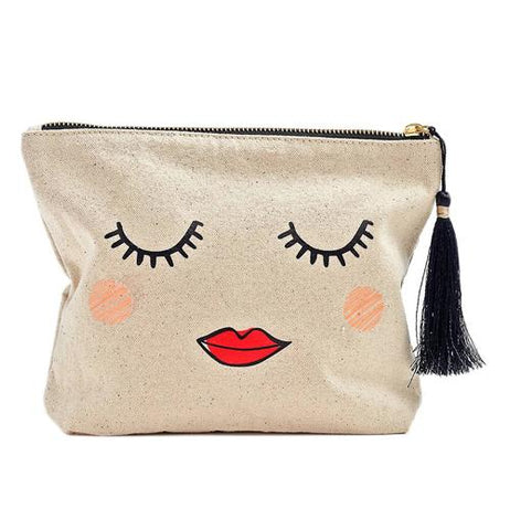 This cream colored bag with a black and yellow zipper has a design of a woman's face with closed eyes, rosy cheeks, and red lips. A black tassel hangs from the zipper.