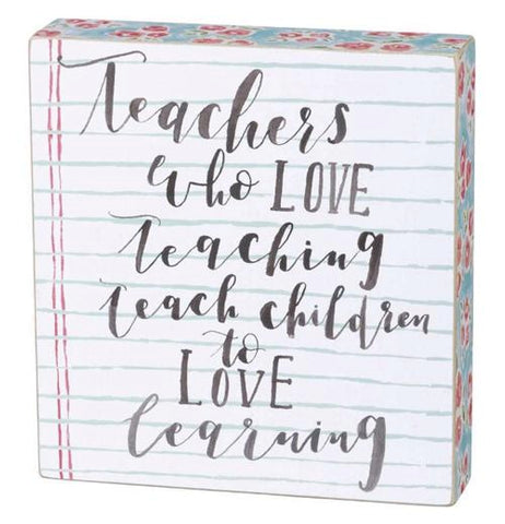 "This wooden box sign has a binder paper design with the words, ""Teachers who Love Teaching teach children to Love Learning"" in black lettering."