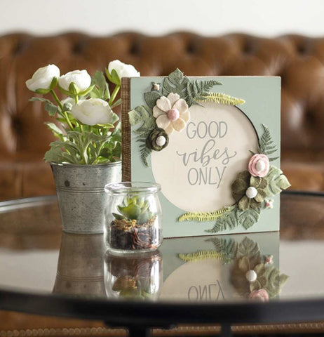 The green sign with the white circle and floral designs is shown sitting on a glass table next to some flowers.