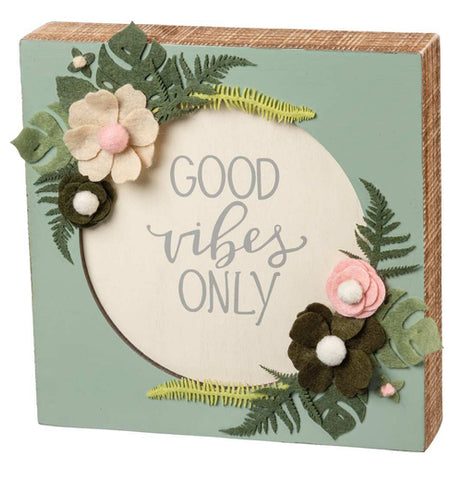"This green wooden box sign has a white circle in its middle surrounded by green and white flowers with green leaves. In the middle of the white circle are the words, ""Good Vibes Only"" in gray lettering."