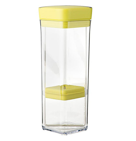 This rectangular glass storage container has a yellow lid at the top and a yellow holder near the glass bottom.