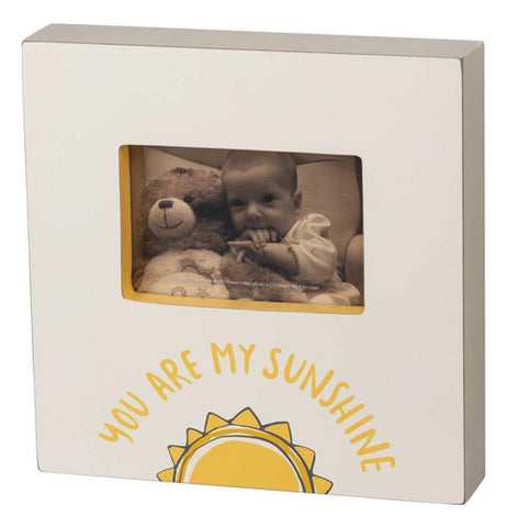 "This gray box frame has a picture of a baby with a teddy bear. Below the picture are the words, ""You Are My Sunshine"" in yellow lettering above a picture of the sun."