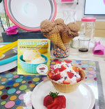 This shows the cookbook SweetSpot along with a dish of three cones of chocolate ice cream and a strawberry dish and some strawberries in front of it front of it. These things are on a blue mat with multi-colored circles on it. All of this is in a kitchen with a plate, bottle, and a glass, with a bit of fluid in the bottom.