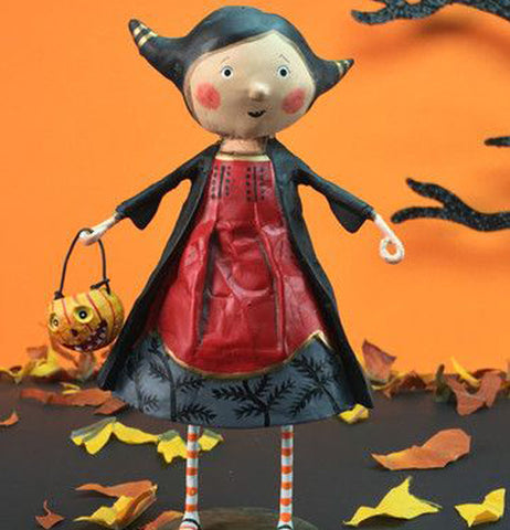 The Veronica Vampire Figurine stands outside in a somewhat fall-like Halloween place.