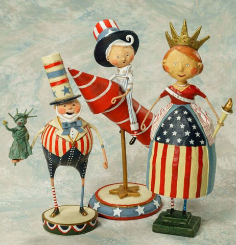 The Pete figurine is shown sitting on a table next to two other independence day figurines.
