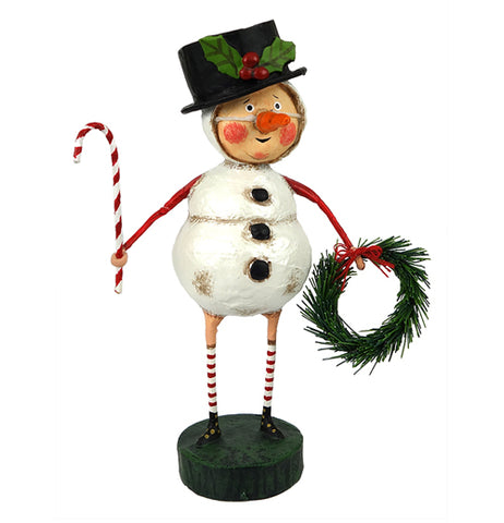 A rosy-cheeked man in a snowman costume holding a wreath and candy-cane while wearing a black top hat with holly on it
