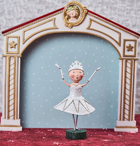 This Snow Queen is in a white dress with a tiara and holding her hands up on a stage.
