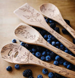 The wooden spoon with the image of a bird is shown with other wooden spoons with similar designs.