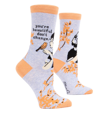 "The pair of ""You're Beautiful"" Crew Socks for women features orange and blue with a woman holding a bird on her finger and words that says, ""You're Beautiful Don't Change"" in change."