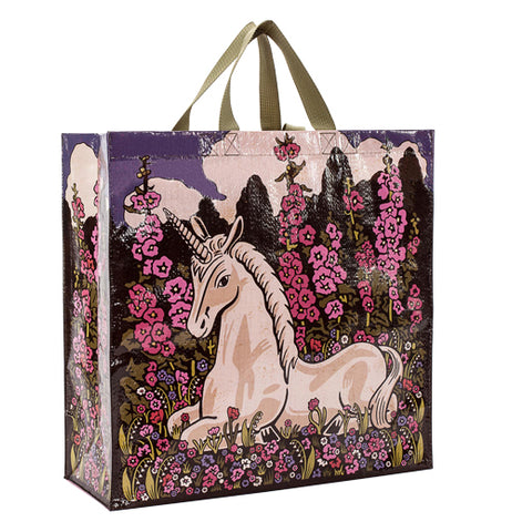 This Shopper bag shows a unicorn sitting on a field of pink and purple flowers.