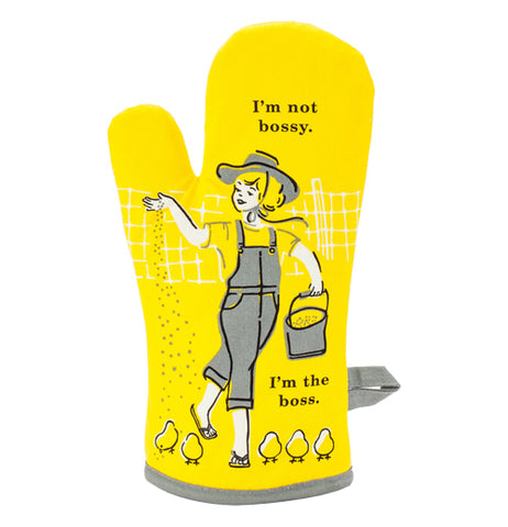 "This oven mitt has a yellow fabric featuring a farmer girl in a gray hat and overalls feeding baby chicks with a black text above and below that says, ""I'm Not Bossy, I'm the Boss""."