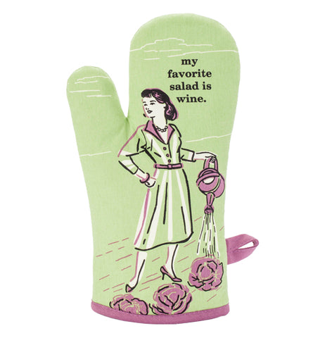 "This oven mitt has a light green fabric with a woman in 1950's garb watering lettuce in purple and white details with a text in black that says, ""My Favorite Salad is Wine""."