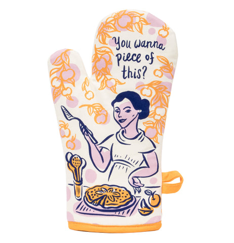 "A Picture of a orange and white oven mitt with a picture of a woman holding a pie server and standing in front of a pie while saying ""You Wanna Piece of This?"""