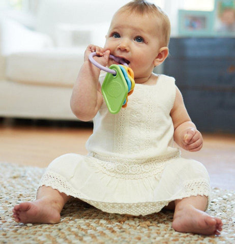 a baby in a yellow dress with the key baby toy in its mouth playing on the carpet.