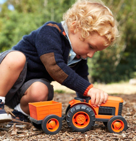 A boy playing the orange truck on the ground.