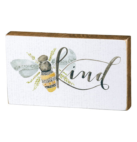 "This white box sign features a design of a honey bee next to some black text that reads, ""Kind""."