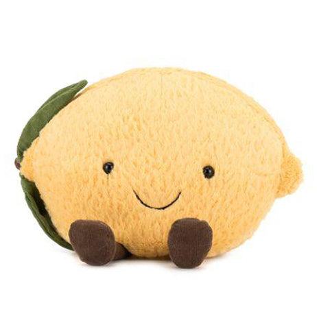 Front view of yellow plush lemon with green leaves on the side along with a smiling face and brown feet on a white background.
