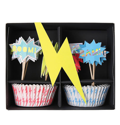 "The black package of the ""Super Hero"" Cupcake Kit has a yellow lightning bolt and shows cupcake wrappers and the toppers."