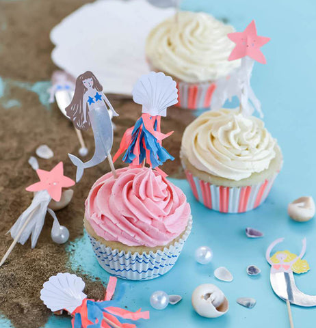 "Three cupcakes made with the ""Let's Be Mermaid"" Cupcake Kit. Two cupcakes are topped with yellow frosting that has pink striped wrappers and one with the pink frosting that has the blue wave wrapper and also shows a mermaid, seashell and starfish cupcake toppers."