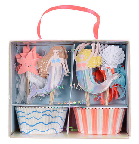 "The ""Let's Be Mermaids"" Cupcake Kit box has 2 sets of wrappers in 2 styles one is white with blue waves, the other features pink and white vertical stripes with with 4 styles of cupcake toppers, two mermaids one is brunette and one is blond and two styles of seashells."
