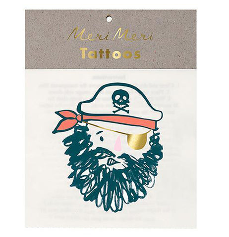 "This front view of a stack of temporary tattoos shows a pirate face with a thick black beard, a golden eyepatch, and a red-orange bandanna under a hat with the skull and crossbones logo on it. In gold lettering at the cardboard top of the packaging are the words, ""Meri Meri Tattoos""."