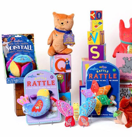 A display of various baby toys including a bird,butterfly and star rattles  along with different sized learning blocks.
