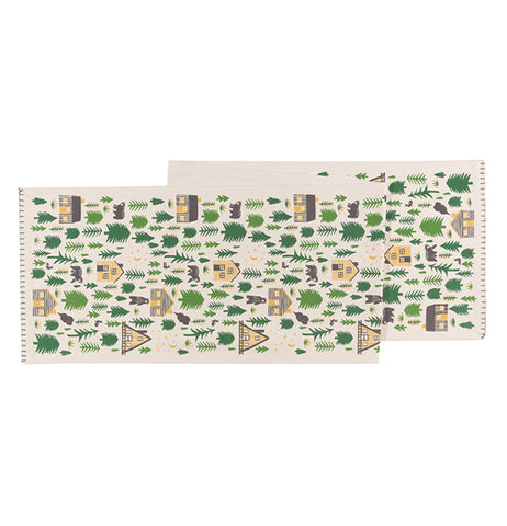 This white table runner features a unique design of brown cabins and black bears in the middle of a forest.