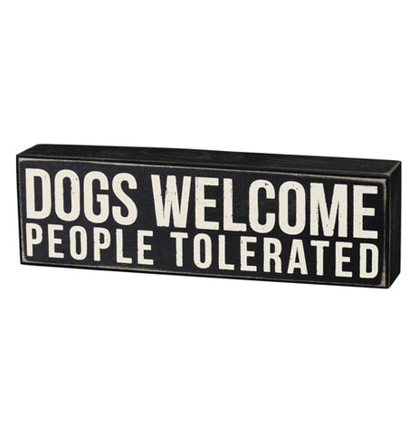 "This rectangular-shaped box sign has white letters on a black background that read, ""Dogs Welcome People Tolerated""."