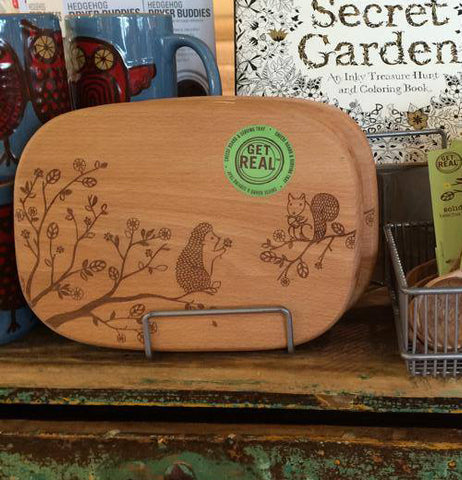 The cheese board with the squirrel and the hedgehog is shown on a wooden shelf.