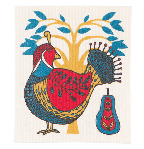 This dish cloth has a picture of a red, gold, and blue partridge standing in front of a golden tree with blue-green leaves. Behind the bird is a blue and red pear with golden seeds.