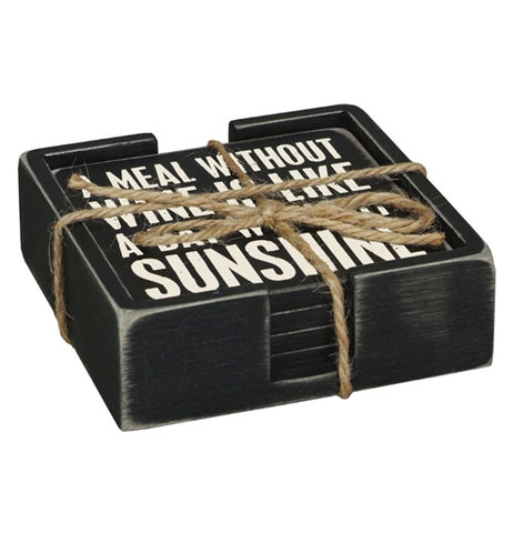 "This black wooden holder contains a set of five black wooden coasters, the top of which reads in white lettering, ""A Meal Without Wine is Like a Day Without Sunshine""."