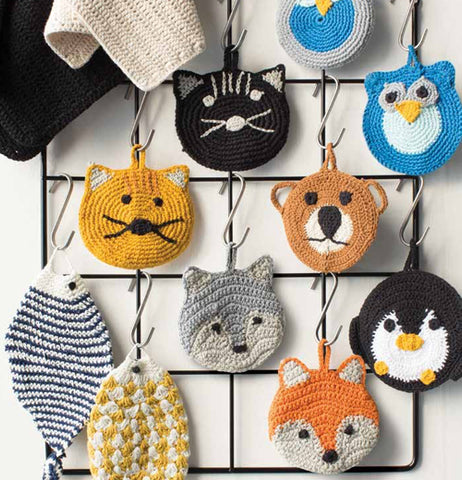 This set of 2 calvin cat tawashi scrubbers hangs from its hook with other tawashi scrubbers ready to clean your dishes.