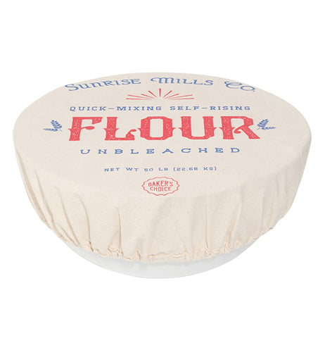 "A white bowl is covered with a cream colored cloth cover with the words, ""Sunrise Mills Com. Quick-Mixing Self-Rising Flour Unbleached"" in blue and red lettering."