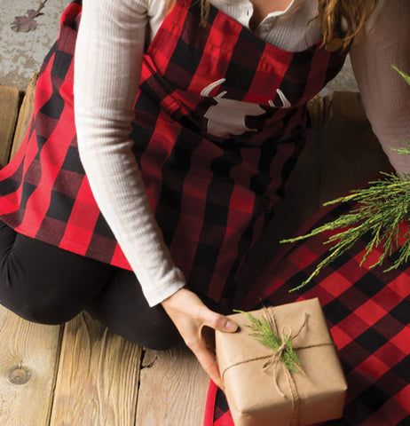 A person wearing the deer apron while wrapping gifts.