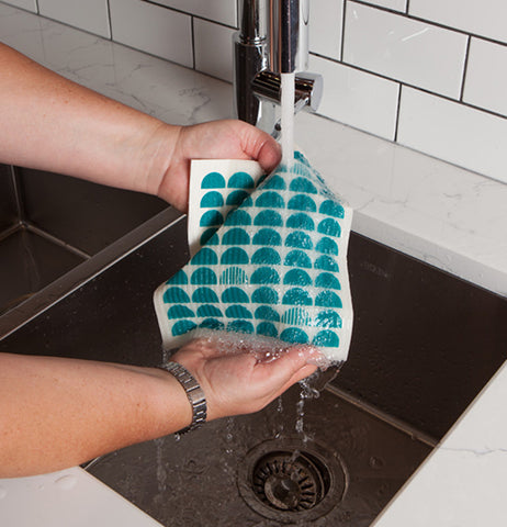 This person is showing people how to wash a green pattern half circle Swedish dishcloth.