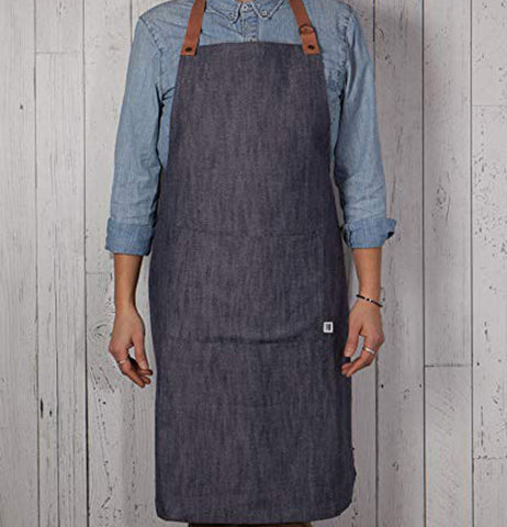 Someone wearing the Denim renew apron that has the adjustable leather neck strap.